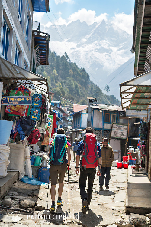 Two trekkers passing through the town of Lukla, Nepal