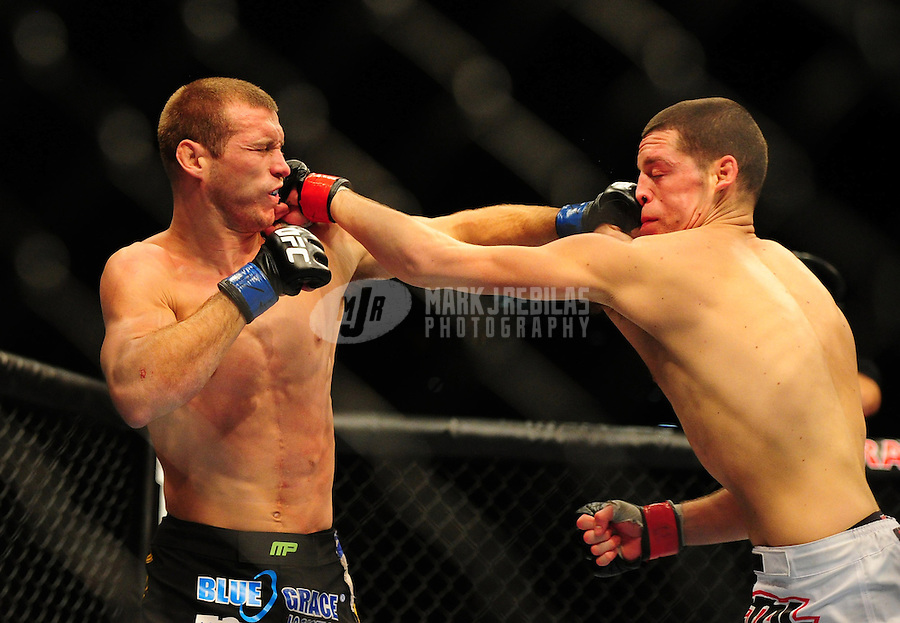 Dec 30, 2011; Las Vegas, NV, USA; UFC fighter Nate Diaz (right) and Donald Cerrone punch each other in the face during a lightweight bout at UFC 141 at the MGM Grand Garden event center. Mandatory Credit: Mark J. Rebilas-