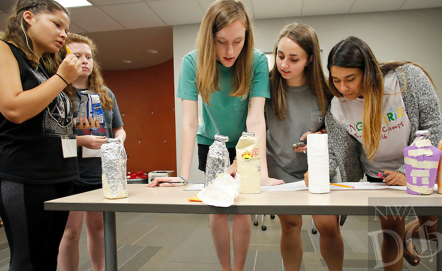 NWA Democrat-Gazette/DAVID GOTTSCHALK  Kaitlynn Stubbs (from left), 14, and McKenzie Taylor, 13, watch Tuesday, July 19, 2016, Hayley Chandler, a junior biomedical engineering student at the University of Arkansas, Molly Churchwell, a junior chemical engineering student, and Miriam Gonzalez, a sophomore biomedical engineering student, record temperatures as they conduct a chemical engineering heat experiment. The two girls participated in a water bottle insulation experiment that is one of the activities taking place at Engineering Girl Camp available to eighth and ninth grade students. The weeklong half day camp is one of four Engineering Summer Camp 2016 offered at the University in Fayetteville.