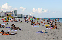 People enyoying the late afternoon sun, sand and warm ocean waters of beautiful South Beach, Miami Beach Florida.