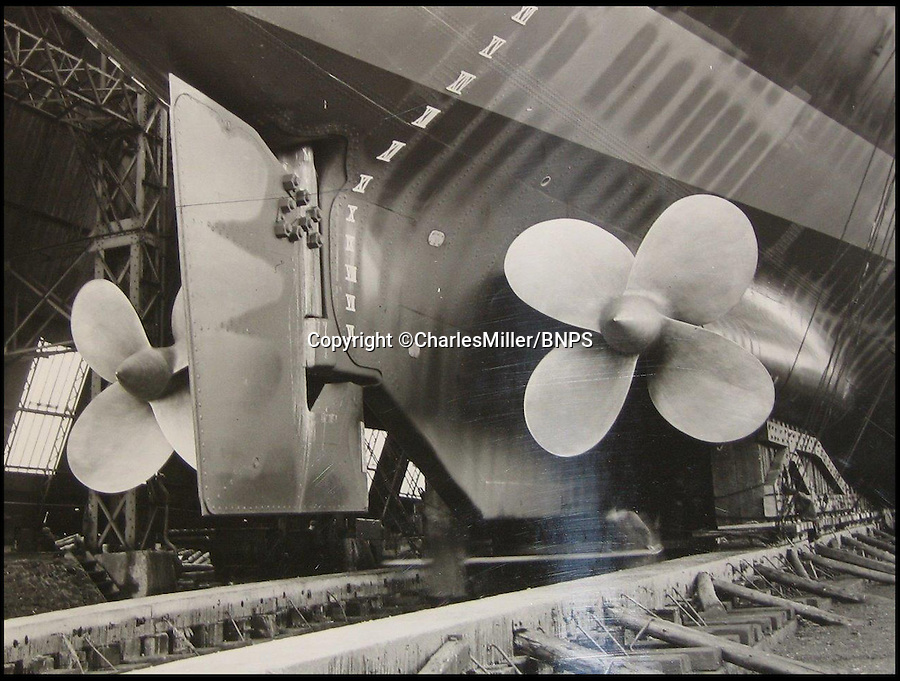 BNPS.co.uk (01202 558833)<br /> Pic: CharlesMiller/BNPS<br /> <br /> ***Must use full byline***<br /> <br /> Prop shaft showing massive bronze propellers.<br /> <br /> Rare photographs showing the complete construction of the much-loved Royal yacht Britannia have surfaced 60 years later.<br /> <br /> The image archive was recorded by shipbuilders John Brown &amp; Co during the 10 months it took to build the 412ft long vessel for Queen Elizabeth II.<br /> <br /> The 70 black and white photos document virtually every stage of the project, from the laying of the keel in June 1952 to the furnishing of state dining room in April 1953.<br /> <br /> They show cloth-capped, blue collar engineers hard at work while management in smart suits and bowler hats carefully inspect the build.<br /> <br /> Some of the shots of the yacht in dry dock show it covered in scaffolding and highlight the two enormous propellers at the stern.