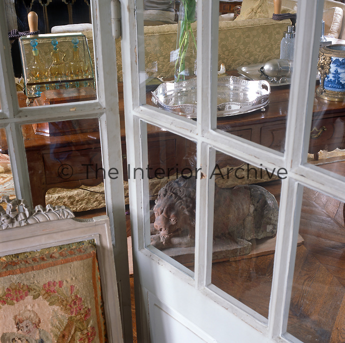 A view through a French window to a sitting room with various items displayed on a sideboard.