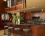 A view of the kitchen, granite countertops and backsplash with a view of the 2nd floor catwalk to the rooftop porch.