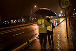 "At 06:00 AM, a copuple waits under an umbrella the comiming of the Korrika. Irun (Basque Country) March 22, 2015. Irun (Basque Country) March 22, 2015. The ""Korrika"" is a relay course, with a wooden baton that passes from hand to hand without interruption, organised every two years in a bid to promote the basque language. The 19th Korrika will run over 11 days and 10 nights, crossing many Basque villages and cities, totalling some 2300 kilometres. Some people consider it an honour to carry the baton with the symbol of the Basques, ""buying"" kilometres to support Basque language teaching. The ""Korrika"" this year ends in Bilbao on March 29. (Gari Garaialde / Bostok Photo)"