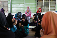 January 13, 2015 - Puchong, Kuala Lumpur (Malaysia). Puan Wan Nur Fauziah (center), admin at the Sekolah Menengah Islam Global Ikhwan school in Puchong, during the lunch prayer. Young female daughters of Ikhwan members attend the school to study arabics, read the Koran and following practical workshops learning how to cook, clean or take care of babies. © Thomas Cristofoletti / Ruom