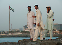 Men gather on the jetty in Dubai before prayer time.