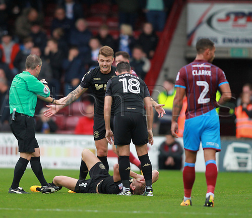 7th October 2017, Glanford Park, Scunthorpe, England; EFL League One football, Scunthorpe versus Wigan; Callum Elder of Wigan Athletic is left on the floor after a painful fall onto the back of his neck in an accidental collision Max Power and Gary Roberts remonstrate with the Ref Mr Robert Lewis