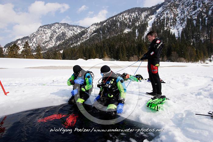Eistaucher sitzen am Eisloch, scuba diver sitting at hole of frozen lake, Plansee, Österreich