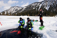 Eistaucher sitzen am Eisloch, scuba diver sitting at hole of frozen lake, Plansee, Österreich