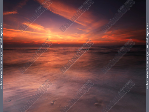 Colorful red sunset over water of lake Huron, Grand Bend, Ontario, Canada.