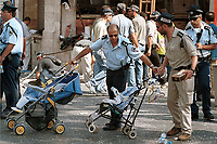 An Israeli policeman rolls away two strollers from the scene of a suicide bomb attack in Jerusalem city center, August 9, 2001. Israeli radio reported 18 people were killed, including six children, and several wounded when a Palestinian suicide bomber blew himself up in a crowded Jerusalem restaurant during the busy lunch hour. Photo by Quique Kierszenbaum