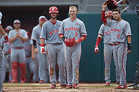 Brett Kinneman (6) of the North Carolina State Wolfpack and his teammates wait at home plate to greet Patrick Bailey (not pictured) after his second home run of the game against the Northeastern Huskies at Doak Field at Dail Park on June 2, 2018 in Raleigh, North Carolina. The Wolfpack defeated the Huskies 9-2. (Brian Westerholt/Four Seam Images)