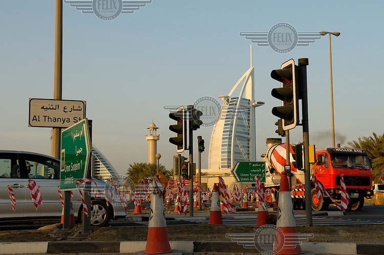 Road works on a junction beside traffic lights with the Burj Al Arab 'seven star' hotel in the distance.
