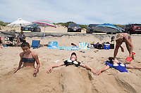 Sisters Chloe, 15, (center) and Amelie Lachance-Soulard, 16 (right), of Ottawa, Canada, and cousin Simone Soulard, 14, lay buried under sand sculptures of mermaid tails at Herring Cove Beach in the Cape Cod National Seashore outside of Provincetown, Mass., USA, on Fri., July 1, 2016. Their aunt Claudine Soulard, of Montreal, helps sculpt the sand. Portions of the parking lot have been closed after land eroded during storms earlier this year. This was the girls' first visit to the area.
