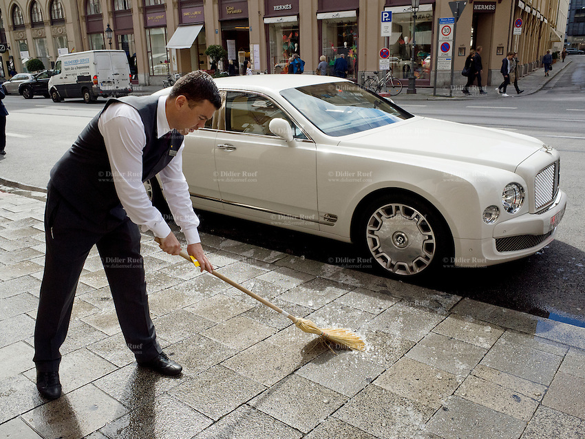 Germany. Bavaria state. Munich. An employee from the 5 star luxurious Hotel Vier Jahreszeiten Kempinski on Maximilianstrasse 17 cleans with a broom the remaining ice from an Ice Bucket Challenge. A white Bentley Mulsanne is parked on the road.  Ice Bucket Challenge, sometimes called the ALS Ice Bucket Challenge, is an activity involving dumping a bucket of ice water on someone's head to promote awareness of the disease amyotrophic lateral sclerosis (ALS) and encourage donations to research. It went viral on social media during July–August 2014. Munich is the capital and largest city of the German state of Bavaria. 26.08.2014 © 2014 Didier Ruef