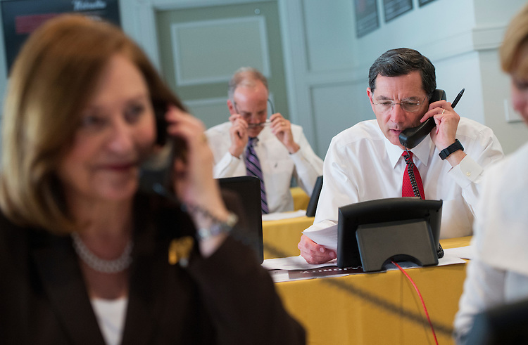 UNITED STATES - JULY 18: From left, Sens. Deb Fischer, R-Neb., Jerry Moran, R-Kan., and Sen. John Barrasso, R-Wyo., make calls to donors during a fund drive at the National Republican Senatorial Committee. (Photo By Tom Williams/CQ Roll Call)