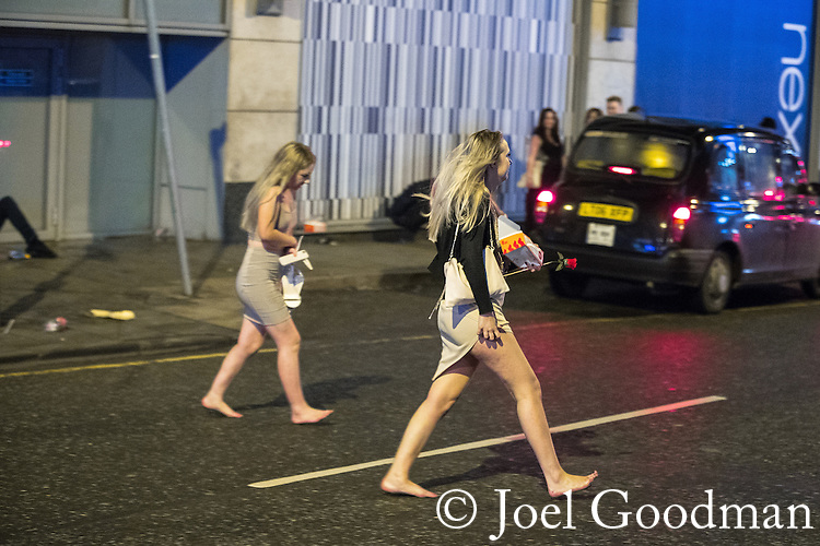 "© Joel Goodman - 07973 332324 . 17/12/2016 . Manchester , UK . Two women cross Withy Grove . Revellers out in Manchester City Centre overnight during "" Mad Friday "" , named for being one of the busiest nights of the year for the emergency services in the UK . Photo credit : Joel Goodman"