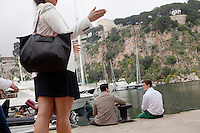 International University of Monaco students Salvatore (left) and Felix (right) spend time on the quayside in the Port of Fontvielle, Fontvielle, Monaco, 19 April 2013. The Prince's Palace of Monaco can be seen at the top of the cliff behind (top centre). Fellow student Louise Cheng talks in the foreground.