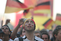German national soccer team supporters intently watch the large television screens at the Fan Festival next to the Brandenburg Gate in Berlin Germany, on July 4th, 2006. On the television was the FIFA World Cup Semi-Final match was won on two late goals in extra-time by Italy, which defeated Germany to advance to the final.