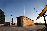 SYRIEN, 07.2014, Koreen (Provinz Idlib). Leben ohne Zentralregierung: Satellitenfernsehschuesseln und eine neue WiFi-Antenne (Mitte) auf einem Hausdach. Es ist das erste Mal ueberhaupt, dass das Dorf Anschluss an das Internet erhaelt. Unterdes hat ein zweiter Betreiber schon ein konkurrierendes Netz installiert. | Life without a central government: Satellite TV bowls and a new antenna for Wi-Fi internet (c) on a rooftop. It is the first time the village gets access to the world wide web at all. In the meantime another operator has set up a second network. Economic competition in times of uncertainty.<br /> © Timo Vogt/EST&OST