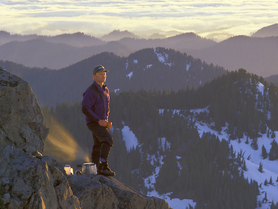 Man standing on rock in mountains drinking hot beverage