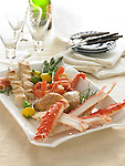 A large platter of seafood with king crab legs, halibut skewers, shrimp, and smoked whitefish. With asparagus and small squash, bottle of champagne, and dishware