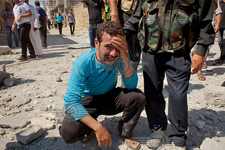 A man reacts moments after his home was destroyed and family members killed by two bombs dropped from Syrian Airforce fighter jets that were targeting the neighbouring Free Syrian Army (FSA) command centre in Aleppo. Eleven civilians from two families died including at least four children.