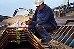 GORINCHEM - Aan de rand van bedrijventerrein Avelingen maakt een lasser van Combinatie De Klerk - Martens en Van Oord met een schop een werkvloer aan de bodem van een stalen damwand voor een nieuwe kade langs de rivier De Merwede. Als onderdeel van Rijkswaterstaat's project Ruimte voor de Rivier, wordt het vrijgekomen zand van een uitgegraven uiterwaard(op de achtergrond), gebruikt voor de betere bereikbaarheid van de watergebonden industrie. Voor het maken van de nevengeul, die tot een waterstanddaling van 10.7 centimeter moet leiden, wordt 900.000m3 grond ontgraven.  COPYRIGHT TON BORSBOOM