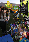Students and residents place items on the memorial outside Sparks Middle School before a candlelight vigil, in Sparks, Nev., on Wednesday, Oct. 23, 2013. On Monday, a 12-year-old student shot and killed teacher Michael Landsberry and injured two other students before shooting himself. (AP Photo/Cathleen Allison)