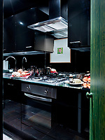 The compact kitchen space is enhanced by the clever use of mirrors.
