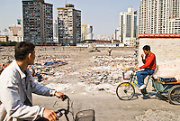 Two men on bicycles riding on Chinese street, Shanghai