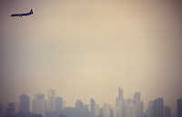 Air pollution. Airplane flies over São Paulo city, Brazil.