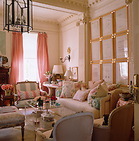 The pretty living room is decorated in soft pastel shades and adorned with many vases of flowers