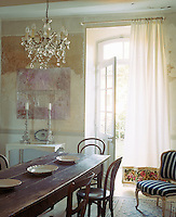 A long linen curtain with an embroidered panel at the bottom shades the dining room from the sunlight that streams through the open door