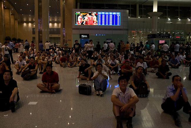 China Olympic fans watch the China vs USA volleyball game at the Tainjin train station while waiting to return to Beijing, China on Friday, August 15, 2008.  Kevin German