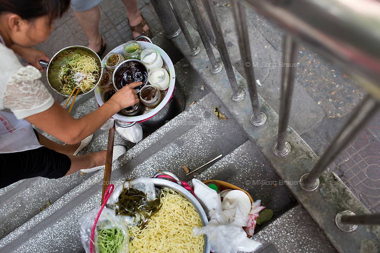 A cold noodle vendor serves customers on the steps of a pedestrian overpass in the central Yuzhong district of Chongqing, China.