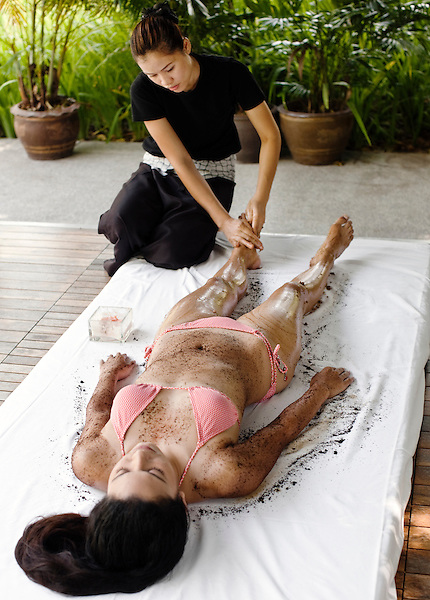 Woman Receiving Coffee Scrub at Indigo Pearl, Phuket, Thailand. A woman receives a coffee body scrub outdoors in a cabana by Indigo Pearl's main pool. The coffee scrub is IN-DI-GO Spa's 30-minute exfoliating treatment that uses a mixture of coffee grounds, carrot and a light aloe vera lotion. Phuket, Thailand.