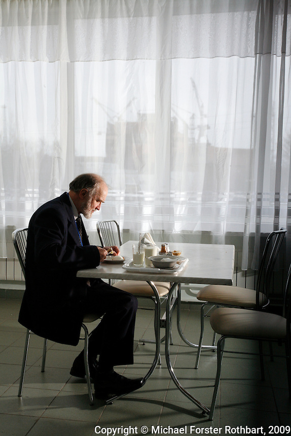 Psychiatrist Viacheslav (Slava) Danilov eats alone in a Chernobyl cafeteria. His research explores how long-term, low-level radiation affects the brain, focusing on the impact of this unique extreme environment on Chernobyl workers. He uses his findings to recommend occupational health procedures for the plant. Visible out the window is the never-finished fifth-block reactor building.<br /> ------------------- <br /> This photograph is part the book of Would You Stay?, by Michael Forster Rothbart, published by TED Books in 2013. The photos come from Forster Rothbart&rsquo;s two long-term documentary photography projects, After Chernobyl and After Fukushima.<br /> &copy; Michael Forster Rothbart 2007-2013.<br /> www.afterchernobyl.com<br /> www.mfrphoto.com &bull; 607-267-4893 &bull; 607-436-2856<br /> 34 Spruce St, Oneonta, NY 13820<br /> 86 Three Mile Pond Rd, Vassalboro, ME 04989<br /> info@mfrphoto.com<br /> Photo by: Michael Forster Rothbart<br /> Date:  2/2009    File#:  Canon 5D digital camera frame 57881