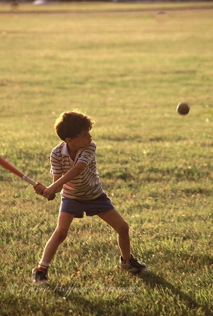 Young boy swinging bat at ball.