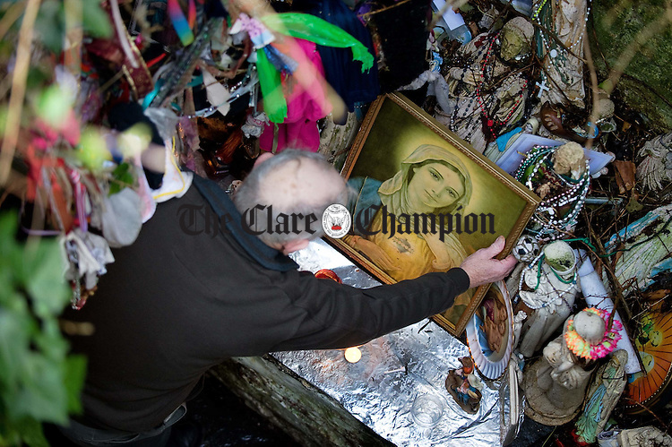 A man touches a picture of Our Lady during his visit to St Bridgid's Well on the feast of St Bridgid. Photograph by John Kelly.