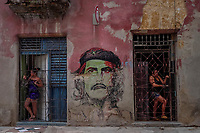 HAVANA, CUBA - JUNE 16: Cubans residents look out from their homes, as a mural of Argentinian revolutionary Che Guevarra is seen painted on wall in Old Havana, Habana Vieja on 16th June, 2015 in Havana, Cuba. <br /> Daniel Berehulak for Panasonic/Lumix