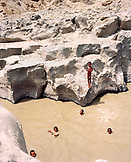 ERITREA, Foro, Bedouin boys swim and cool off in a muddy desert watering hole