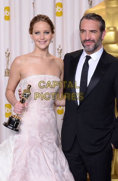 Jennifer Lawrence (wearing Dior Haute Couture) & Jean Dujardin.85th Annual Academy Awards held at the Dolby Theatre at Hollywood & Highland Center, Hollywood, California, USA..February 24th, 2013.pressroom oscars half length white pale pink strapless dress gown voluminous award trophy winner black suit beard facial hair.CAP/ADM/RE.©Russ Elliot/AdMedia/Capital Pictures.