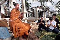 A Buddhist monk performs a ceremony for the victims of the tsunami which struck South Asia on 26/12/2004, in particular the grandson of the King of Thailand who stayed in the bungalow in the background.