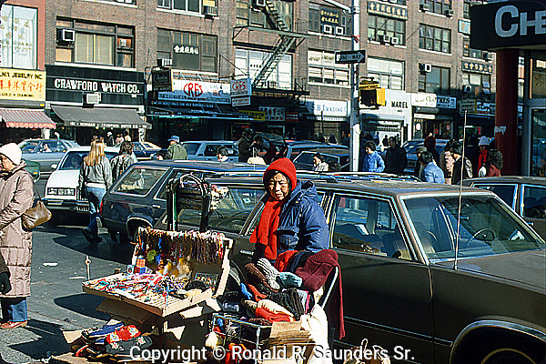 ELDERLY CHINESE WOMAN HAWKS HER WARES in CROWDED CHINATOWN