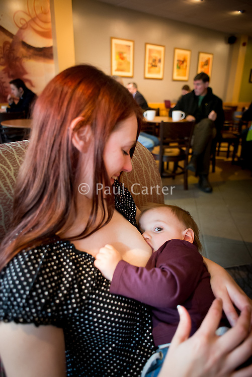 A young woman smiling while looking at her toddler and breastfeeding in a coffee shop.<br /> <br /> Image from the &quot;We Do It In Public&quot; documentary photography project collection: <br />  www.breastfeedinginpublic.co.uk<br /> <br /> Dorset, England, UK<br /> 17/04/2013