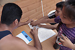 Eleven-year old Juan Lopez studies Braille with Mariano Enriquez at Piña Palmera, a center for community based rehabilitation in Zipolite, a town in Oaxaca, Mexico. Juan's sister Yarelly, who is sighted, lends a hand guiding his fingers along the page.