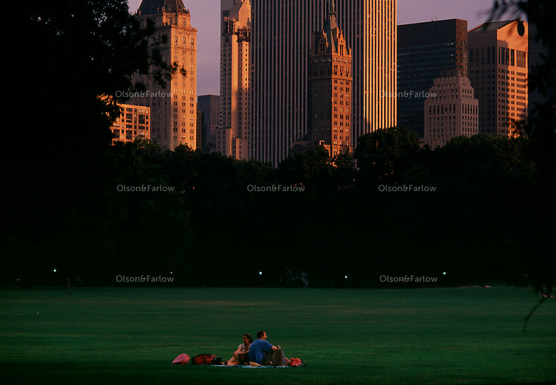 A couple sits alone in Central Park's sheeps meadow under the towering building lining the park. Frederick Law Olmsted believed in the restorative effects of natural scenery to counteract what he saw as the debilitating effects of the modern city.