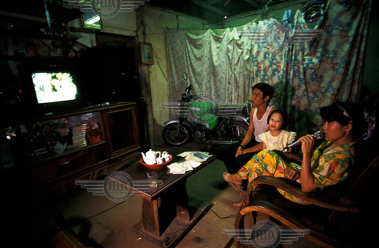 Family, in Dien Bien Phu, north Vietnam, singing along to a karaoke video in the living room of their home.  The bedroom is behind the curtain, and their motorbike takes pride of place, out of the rain.  Credit: Chris Stowers.