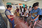 "Larren Jo ""LJ"" Bacilio, a teacher in the Alternative Learning System of the Kapatiran-Kaunlaran Foundation (KKFI), prays with his students at the beginning of class in the Tondo neighborhood of Manila, Philippines. <br /> <br /> KKFI is supported by United Methodist Women."